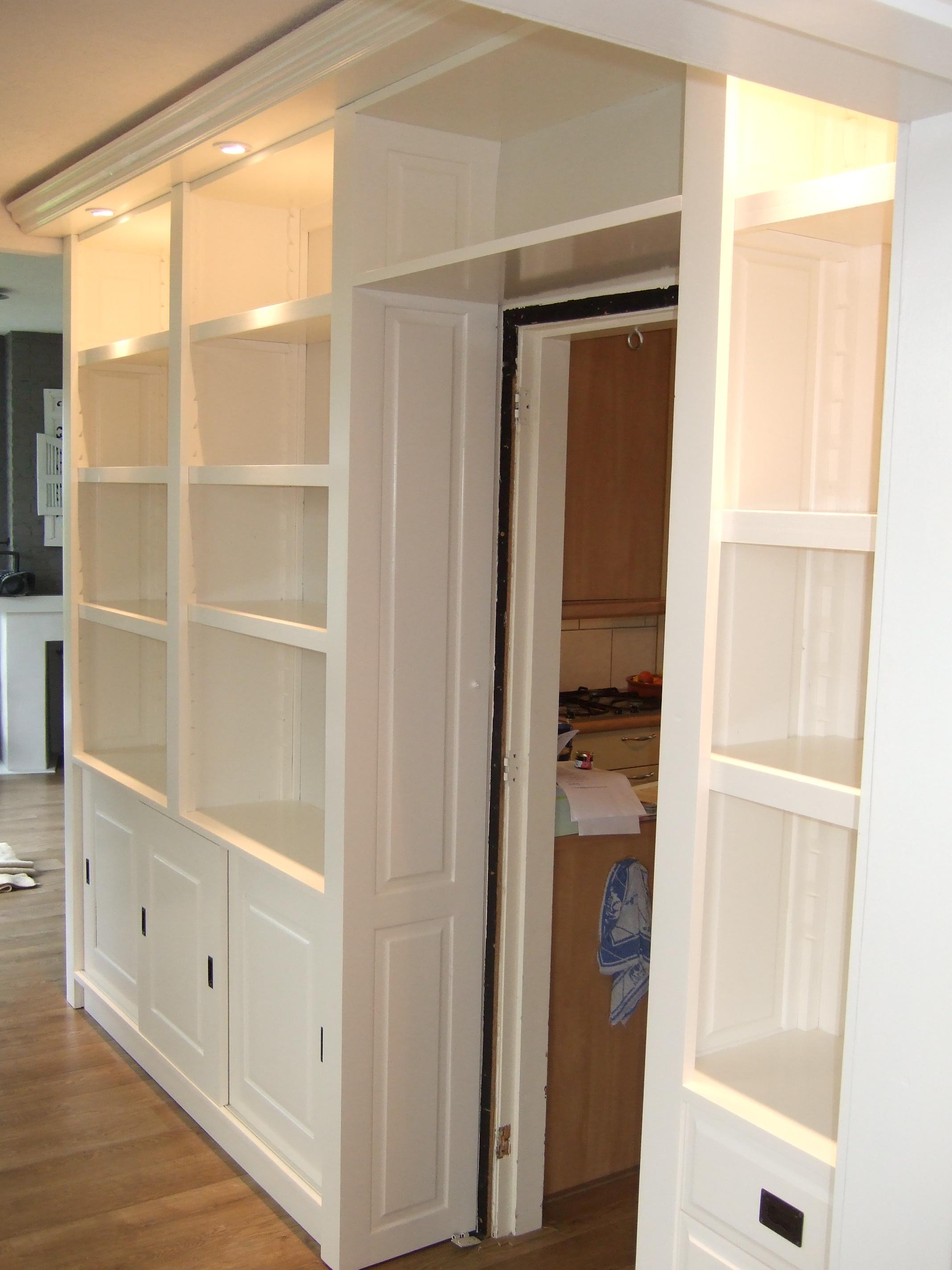 boekenkast met onder een dichte kast boven is een open boekenkast de kast is om een deur gebouwd